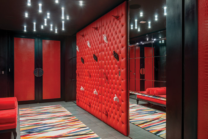 A quirky red padded leather panel set with porcelain hands greet arriving guests
