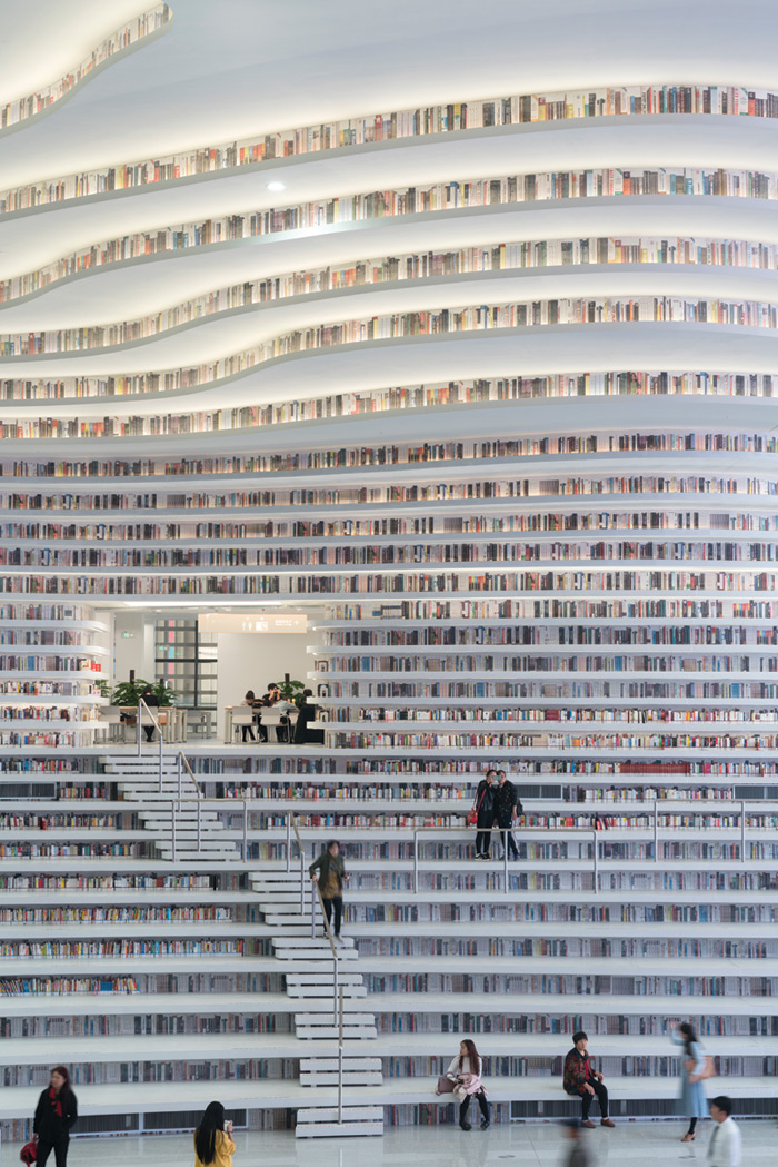 MVRDV, in collaboration with local architects at TUPDI, created China's Tianjin Binhai Library, a 33,700 sq m cultural centre including a spherical auditorium and seemingly endless shelves mixing real books with aluminium graphics in hard-to-reach areas. The scheme also includes meeting rooms and educational facilities. Image Credit: Ossip