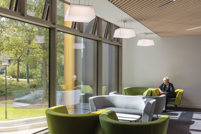 A shared breakout space takes full advantage of the building's woodland setting