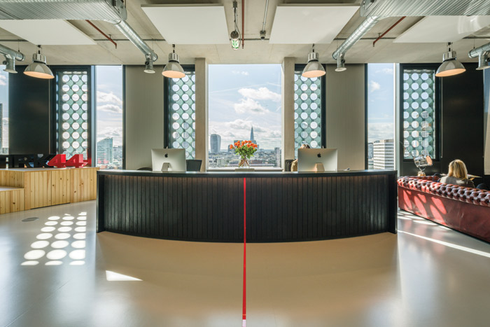 Sitting in front of the London skyline, the black-metal topped reception desk sits on charred timber cladding, with a red line in Plexiglas running down the front and across the floor
