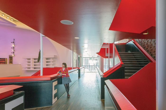 Red steel stairs and walkways in the building's original proscenium arch lead visitors to the new facilities