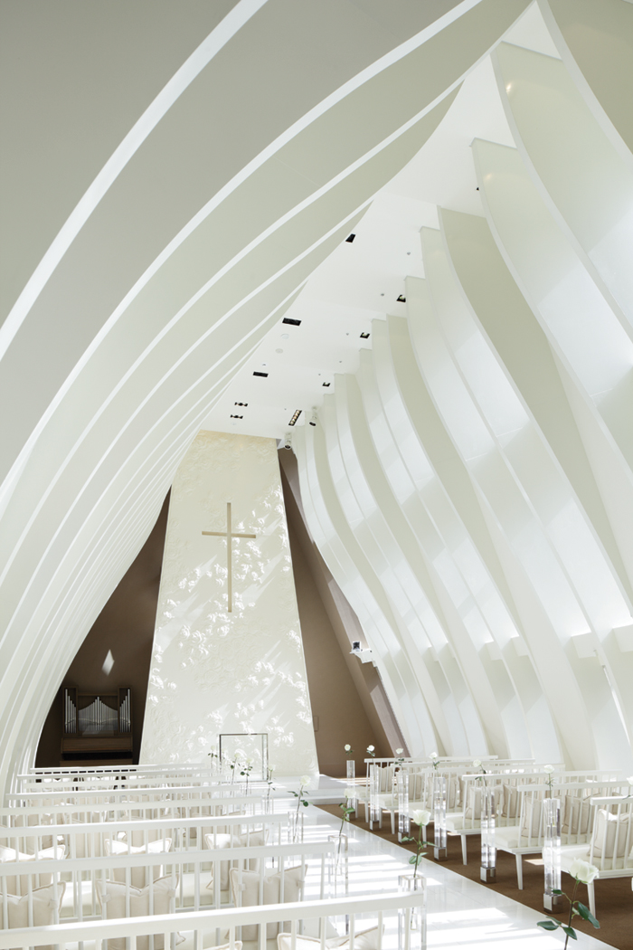 A soaring feature wall of glass-enforced gypsum and blooming white roses by Hsiu Chi Wang sits behind the altar