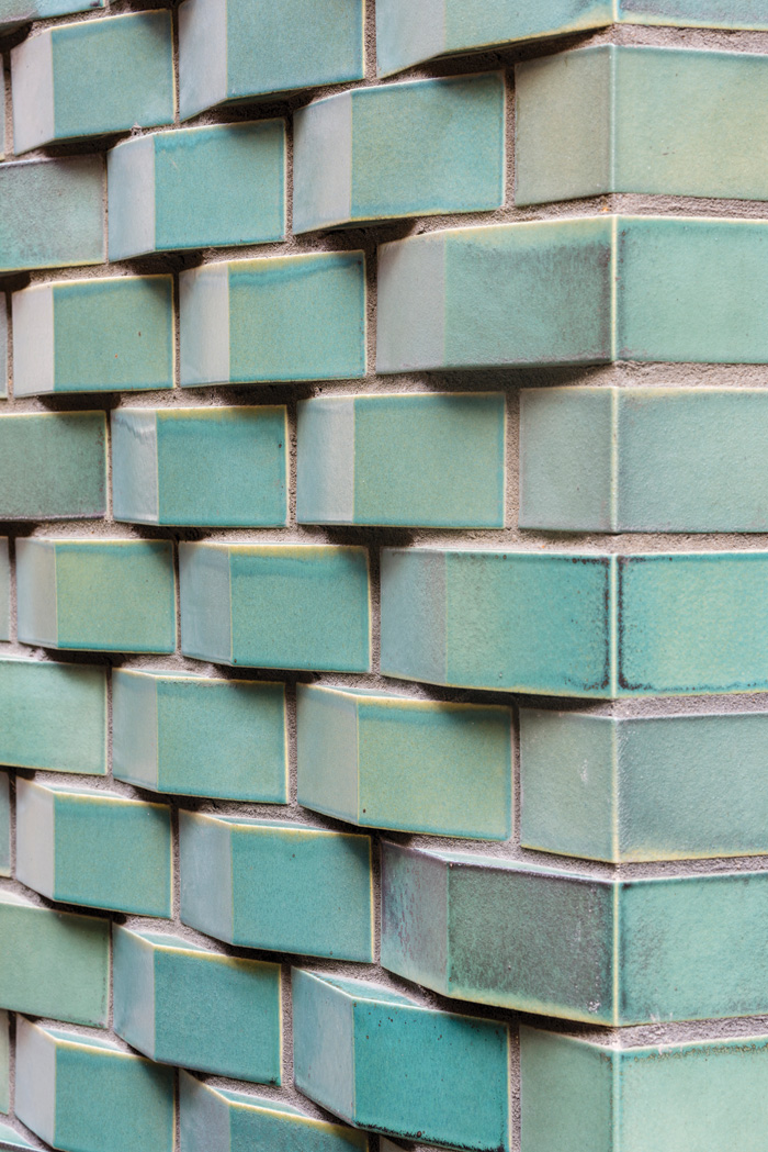 The new woven facade is in a fired green-glazed Umbra Sawtooth brick