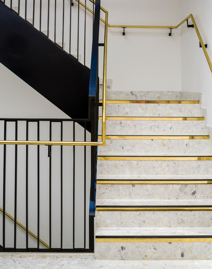 White terrazzo stairs and black balustrade are contrasted with goldcoloured tread edges and handrail