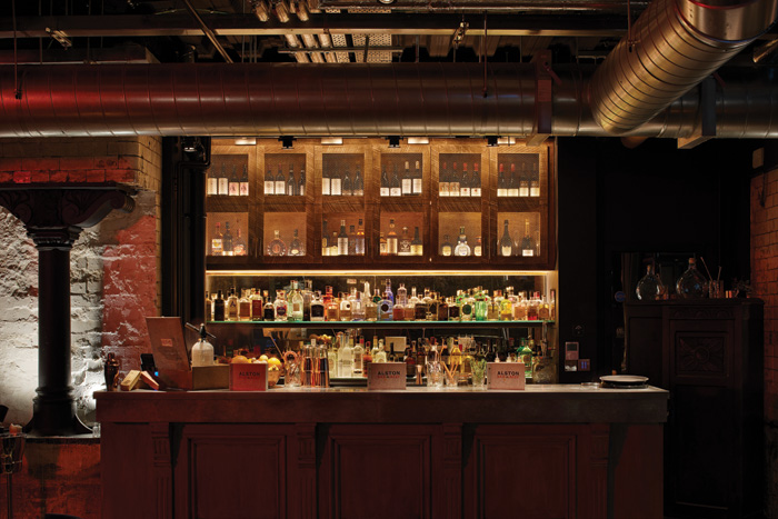 The Speakeasy section of the venue has a glowing bar amid exposed brickwork and wrought-iron pillars