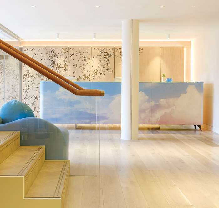 The serene reception area has pale oak flooring and a cloud-graphic fronted desk