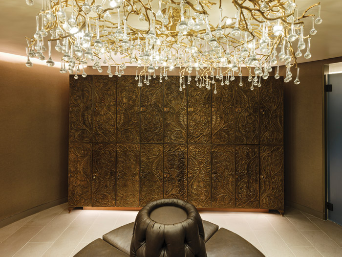 The women's changing room has embossed locker doors and contemporary chandelier lighting