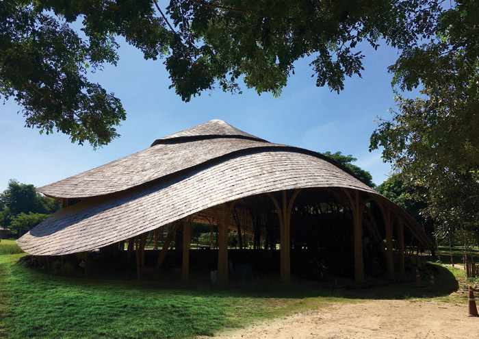 The roof, which is covered in wooden shingles, drops down in three tiered levels, its structure and shape inspired by the lotus flower