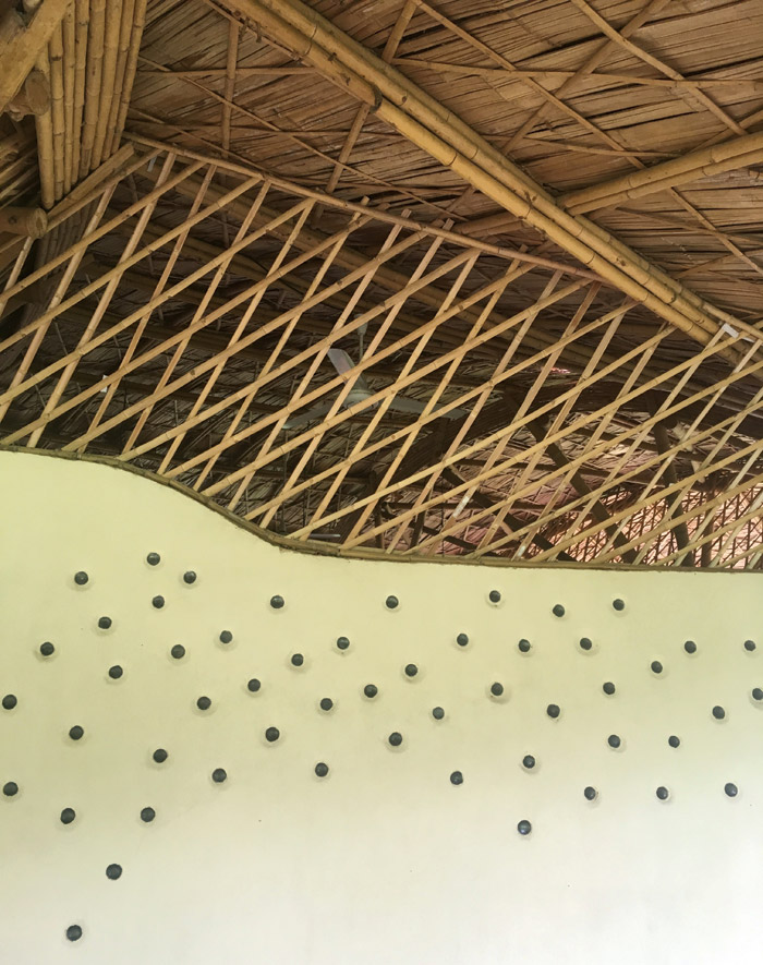 To maximise solar shading, the classrooms' south facing walls are made of rammed earth, which daylight can penetrate thanks to small round glass tiles embedded in the wall