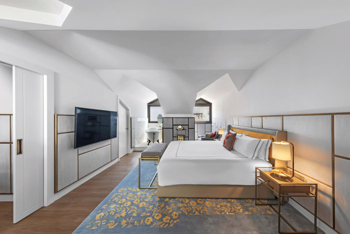The white-painted guest rooms sees the geometry of the bed frames echoes around the TV wall