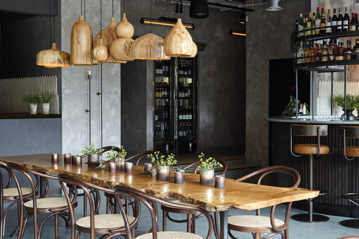A communal table of single piece of rough timber has turned-wood lights over by Tamasine Osher Design