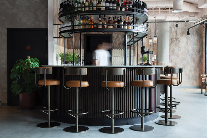 The horsehoe-shaped bar is fronted with dark timber and topped with mint-green Lavastone by Pyrolave