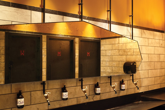 An industrial elements are used in the bathrooms, with a blackened communal trough sink and black water pipes, albeit with gold-coloured taps