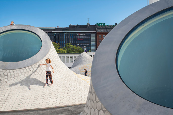 The mounds of Lasipalatsi Square curve up into angled skylights. Image Credit: Mika Huisman