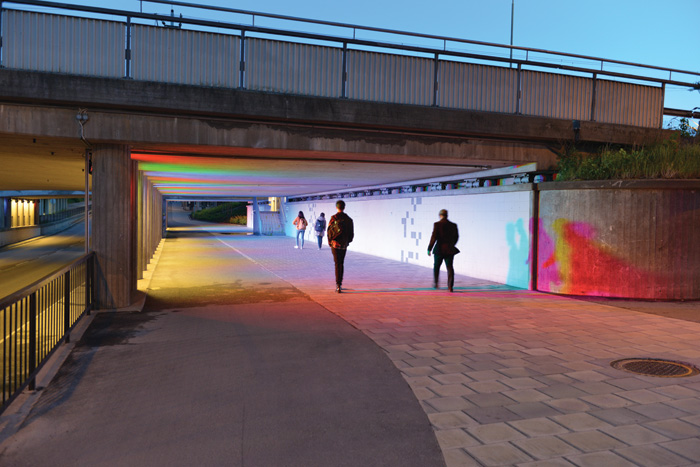 Single-colour fixtures in red, green and blue are evenly spaced between pillars, casting shadows from users as they pass by or play in the light.