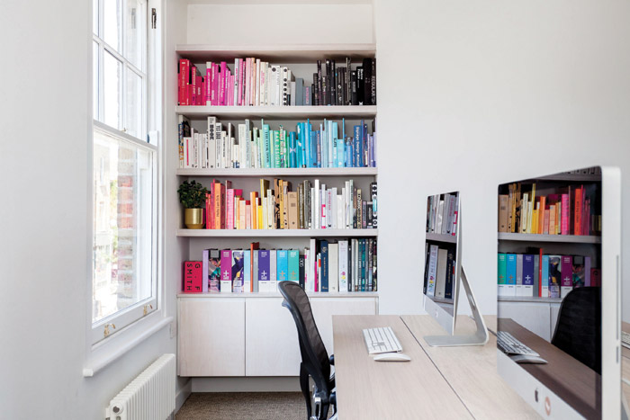 The studio space contains a full-height bookcase, where the contents are ordered by colour