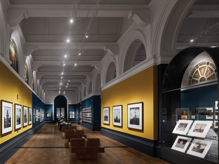 The petrol-blue and mustard-yellow paint palette of the walls was selected to complement the historic painted lunettes lining the upper gallery