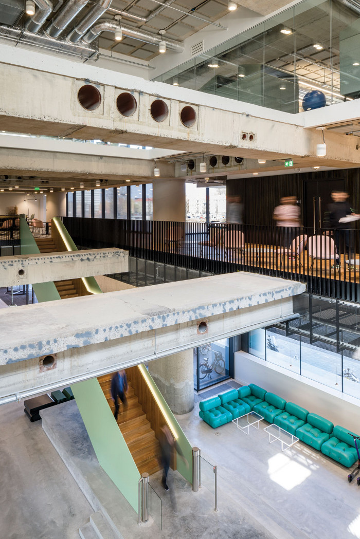 A large staircase leads up to a first-floor area dedicated to meeting and co-working with clients