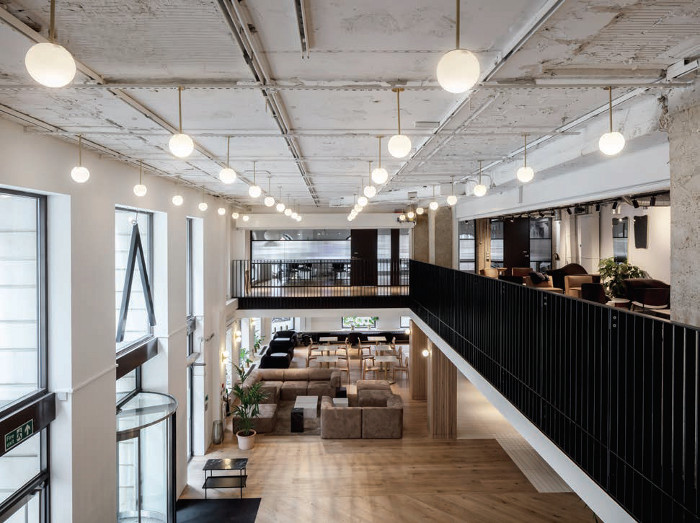 A newly formed double-height atrium is a crucial spatial intervention, and draws natural light into the open plan entrance, which accommodates lounge seating and designated desk spaces for co-working. Image credit: Moxon Architects.