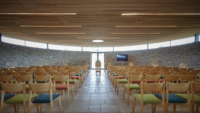 The UK's Harbour View, which opened in 2018, is a private crematorium designed as an alternative to conveyor-belt local authority facilities, with only two services a day taking place. Inspired by Neolithic barrows and stone-lined burial chambers, it has a sedum roof and is surrounded by grassy bunds to limit the visual intrusion on the greenbelt. Local Purbeck stone and subdued lighting create a subtly darkened space in the chapel, while a skylight allows shafts of light to come down onto the coffin. Architect: Western Design Architects. Client: Tapper Funeral Service. Contractor: Glossbrook
