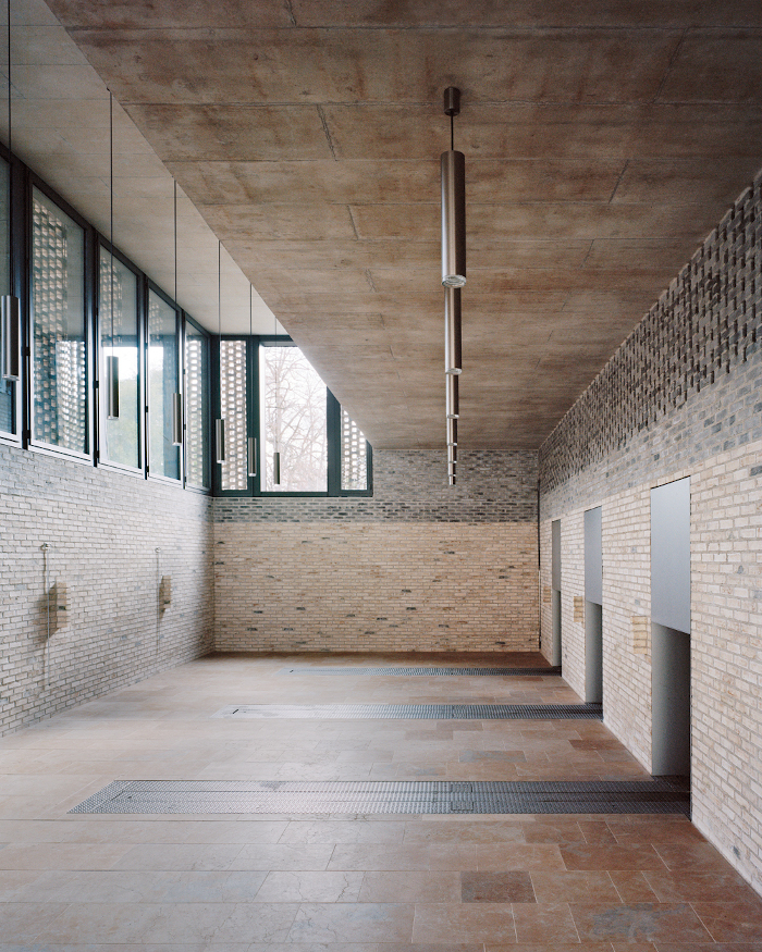 The new crematorium at Basel in Switzerland, opened in 2017, captures in its design the dual nature of the industrial process of incineration combined with the emotional response of mourning. The translation is a building with a concrete structure and a brick skin. The concrete is a rough, industrial product, the brick is a handmade and hand-laid material. The bricks stretch around the building and are open to light and air, defining a porous border that is open and closed at the same time. Architect: Architekturbüro Garrigues Maurer GmbH, Zürich, with collaborators Bernhard Maurer, Frédéric Garrigues and Eleonora Bassi. Client: Immobilien Basel Stadt. Structural engineer: Bollinger und Grohmann GmbH. Landscape: August + Margrith Künzel Landschaftsarchitekten AG, Binningen. Image credit: Rasmus Norlander.
