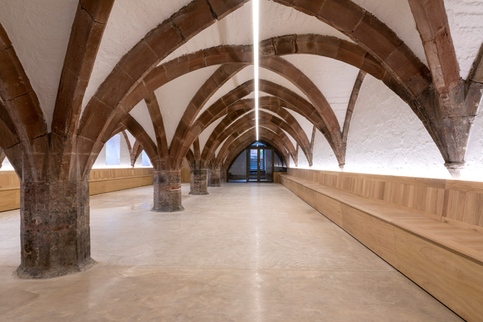 The undercroft below features built-in oak benches and a poured concrete floor