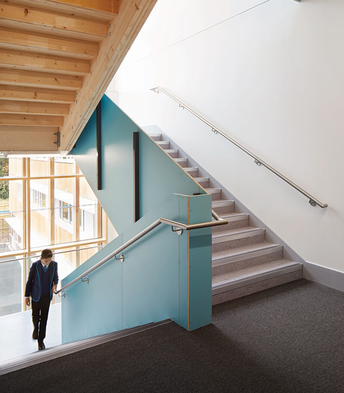The school's signature teal is used in the stairwell
