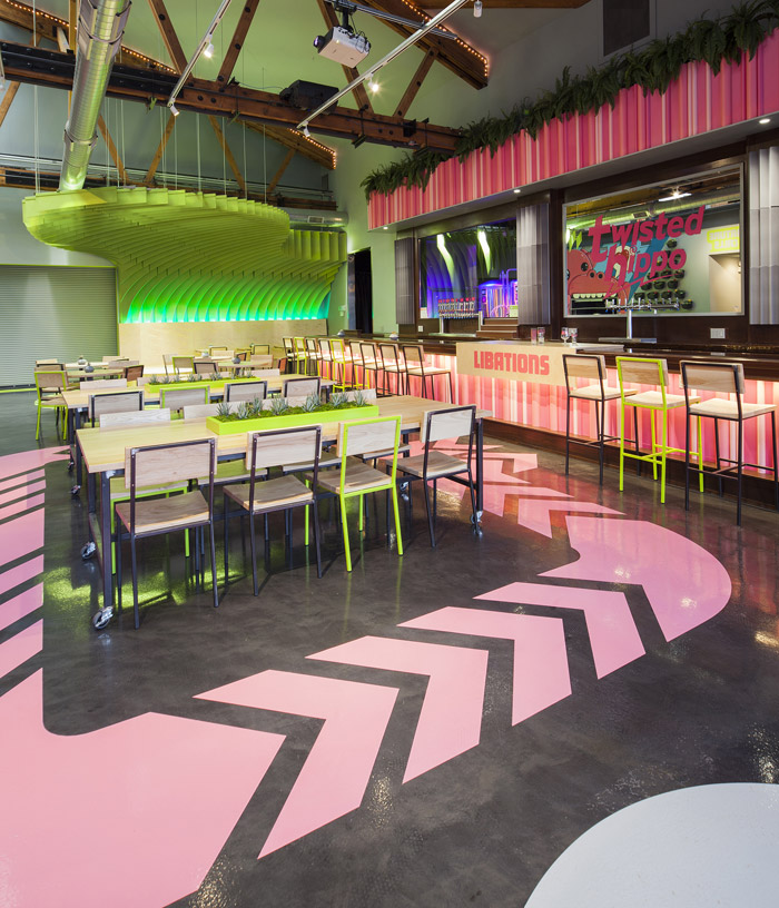 Twisted Hippo, Chicago Twisted Hippo, a brewpub in Chicago, is set apart from the usual sterile, industrial feel of such venues, with bright colours and fun features throughout, including pink direction signs on the floor and a bright green canopy. Design Could Be Architecture General contractor Helios Construction Signage Right Way Signs Felt Fabrication TURF