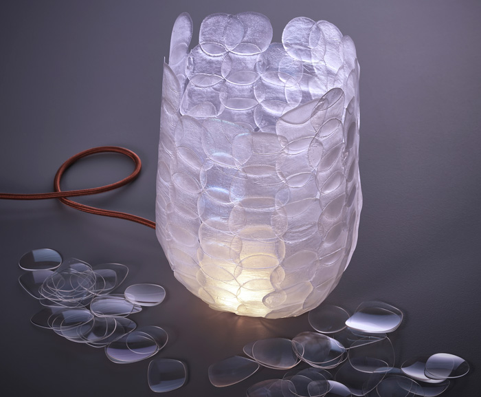 The collection is a series of sculptural lights that repurposes waste lenses into an innovative material