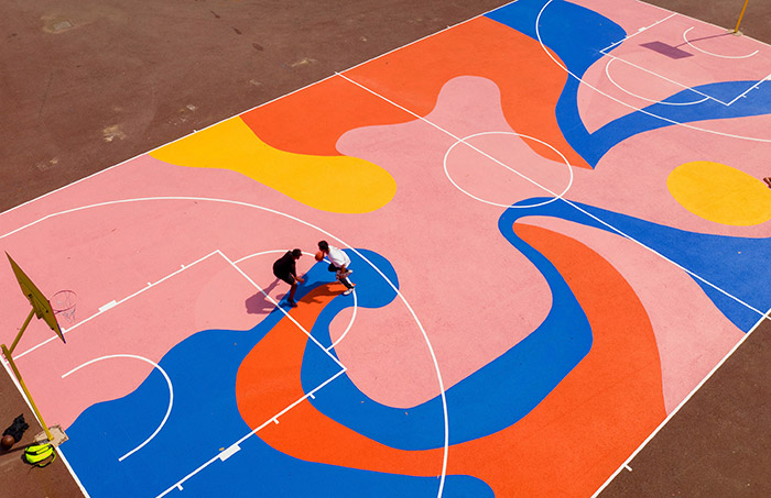 Basketball court transformation in Perth, Australia: This basketball court in Perth, Australia, is just one of a number of courts O'Hara has transformed in recent years. The design hopes to capture the movement of the players, their energy and activity translated into bright colours and fluid shapes. The bright colours are meant to boost the social and endorphinboosting effect of sporting activity, as well as drawing in passers-by.