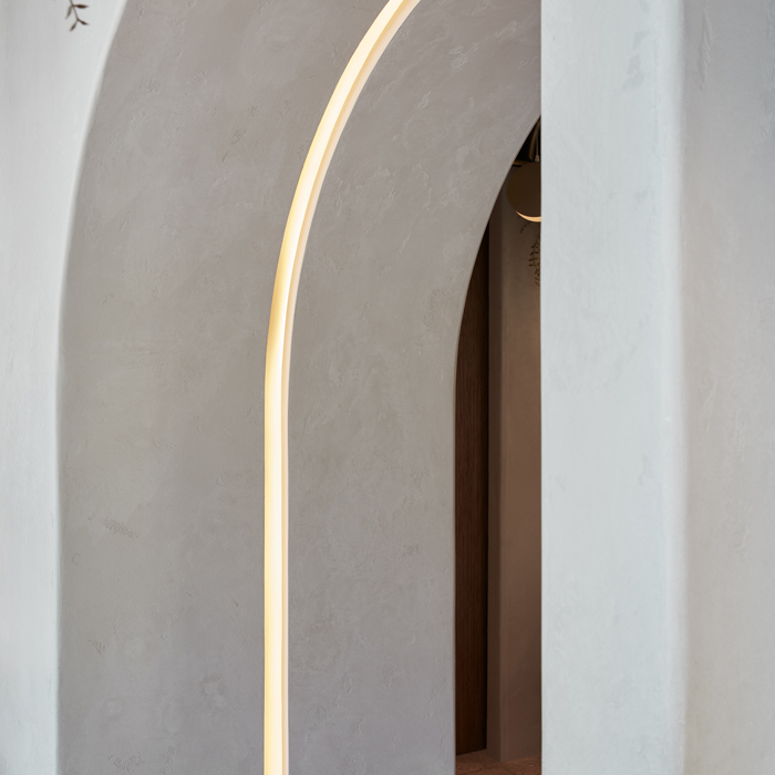 For key points of transition, there are plastered archways or 'portals.' Echoing the curves of the arched pipes, their forms are highlighted by a strip of recessed lighting within the plaster surface