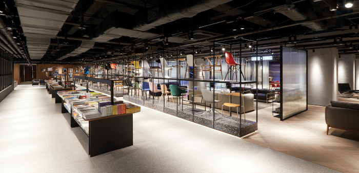 A chair wall on the first floor features dark terrazzo and a blackened frame, and holds a display of 54 iconic products
