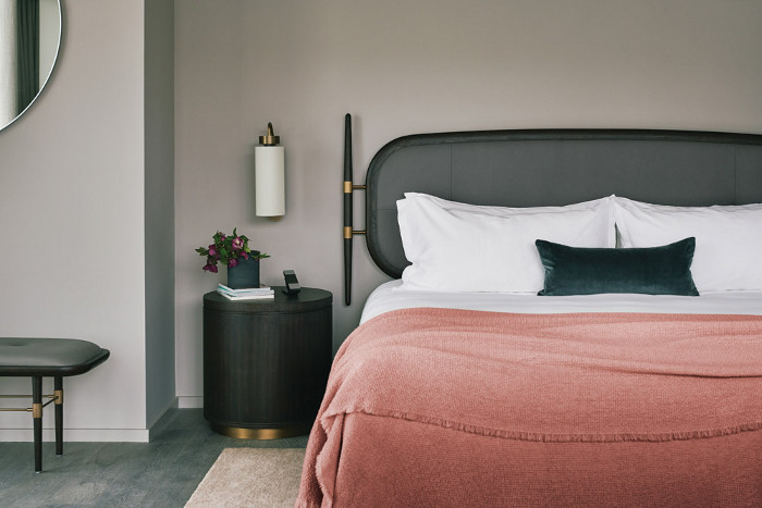 Spacious and modern guestrooms feature softly curved upholstered shapes and stone-clad bathrooms. Image Credit: Rich Stapleton