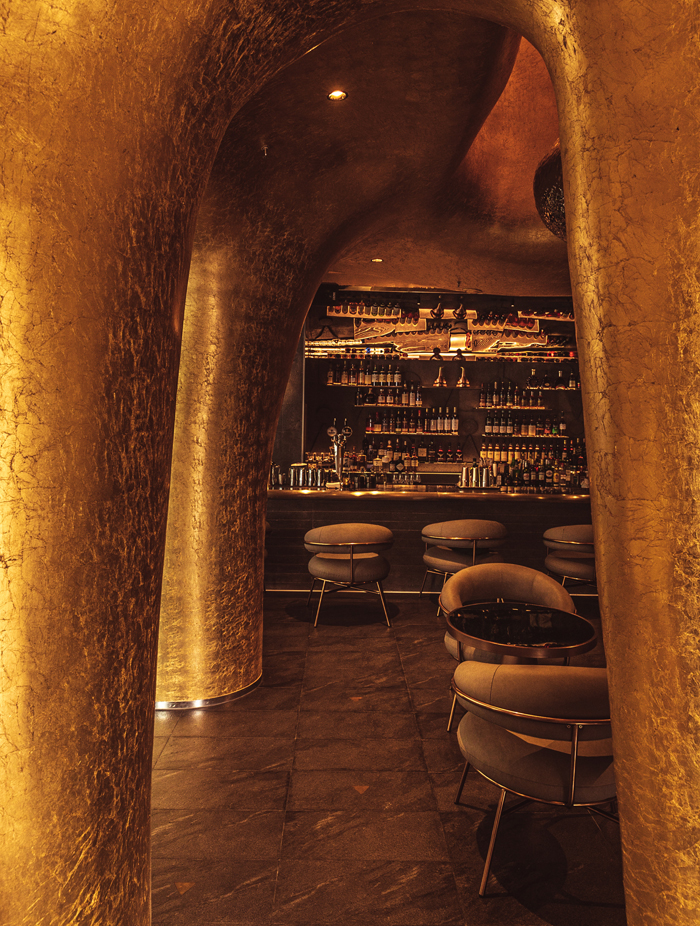 The strange golden, specular wall surfaces are supplemented by subtle lighting. Image Credit: Ringin' Studio