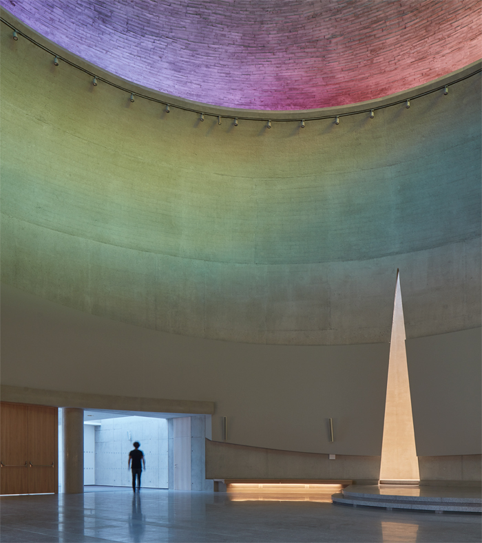 The church initially seems austere for a Catholic place of worship, until the observer looks up to see the play of dynamic, multicoloured light across the concrete walls. Image Credit: Boysplaynice