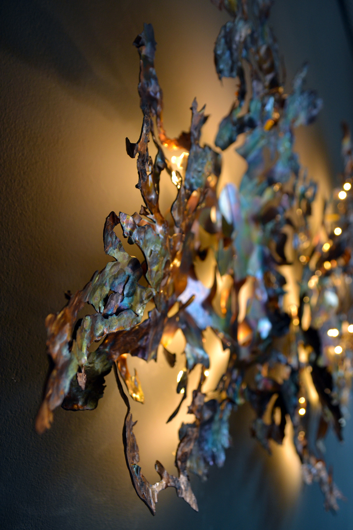 The hand-beaten copper design of the Copper Leaf Chandelier from Jonathan Coles is inspired by the branches of a cedar tree
