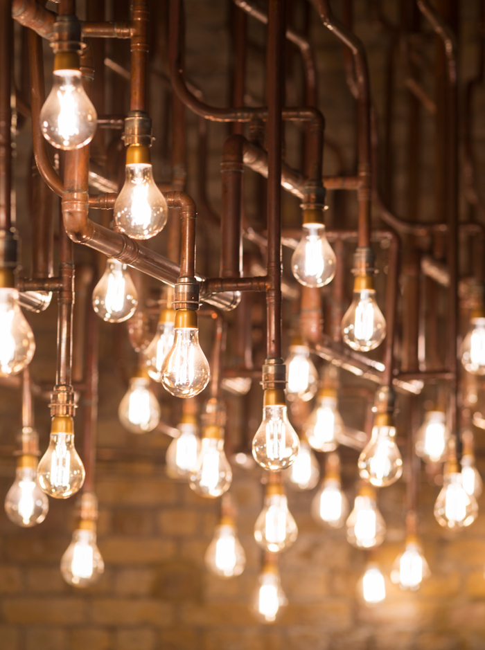 StudioFractal's copper lighting installations have brightened CP Hart's Waterloo Station showroom since 2015