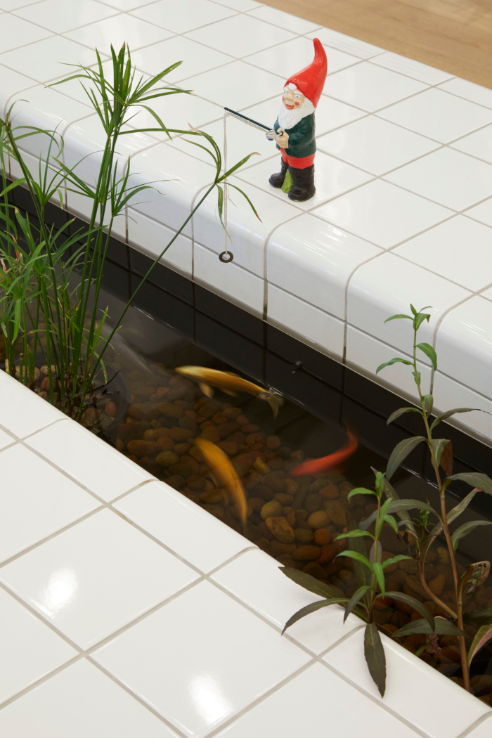 A garden gnome, fishing over the pond – a playful detail of an unusual office building