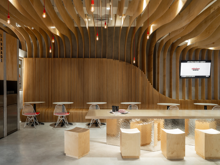 Gretaproject made ripples and curves a theme in the project, opting for a slatted ceiling that undulates like an inverted wooden wave. Image Credit: MIKHAIL LOSKUTOV