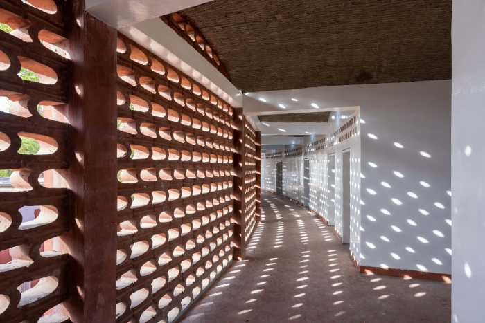 Gaps in the 125m-long corridor's walls allow the building to breathe, adapting interior environments to the site's climatic conditions