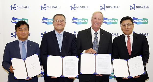On July 23rd, attendees pose for a commemorative photo after the signing for Business Collaboration Agreement and Unit Purchase Agreement for SMR deployment. (From left to right) Jason Jang, Head of Private Equity Division, IBK Securities, Kiyong Na, CEO of the Doosan Nuclear Power Business Group, John Hopkins, CEO of NuScale Power, and Yongjin Song, DHIC CSO