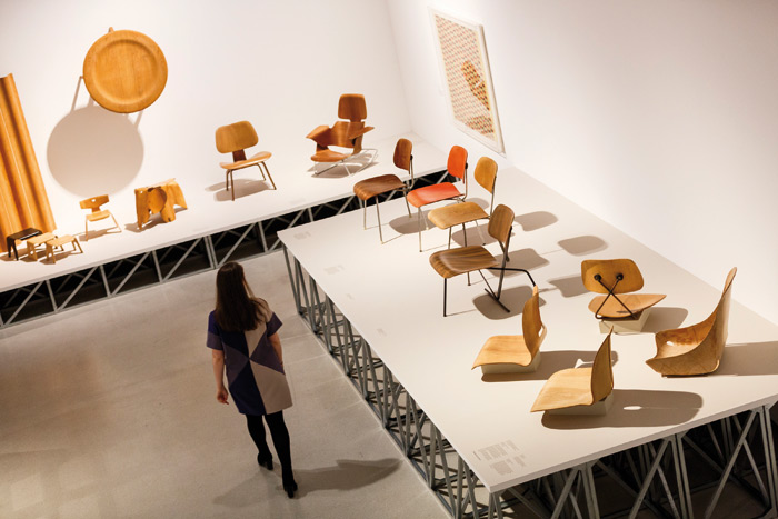A display covering various of the Eameses' plywood chairs