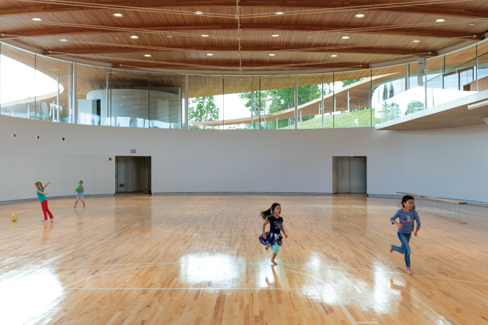 Five 'rooms' sit under the curving canopy roof of the River, including this gymnasium. Image Credit: Iwan Baan
