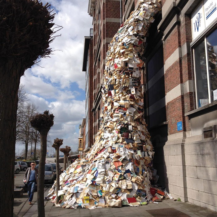 Books are spewed from a window in Alicia Martin's installation Biografias. Photo Credit: Mons2015