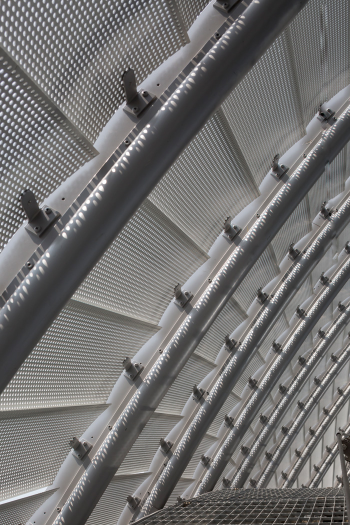 The aluminium lamellas are perforated, allowing light into the upper floors, where they are secured to a steel frame