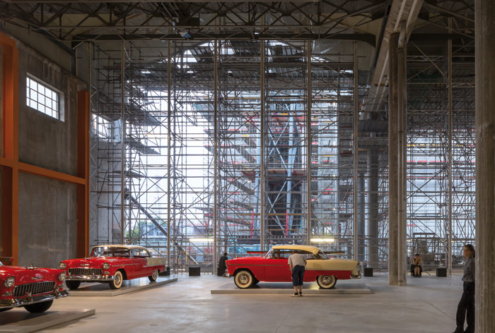 The construction site of the white concrete Torre is visible through the Great Hall, presently littered with cars customised by Elmgreen & Dragset among others