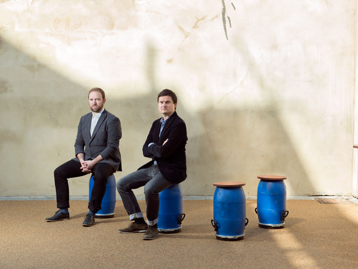 Kevin Haley (left) and David Chambers (right) with stools made of chicken-feed storage bins, part of Roaming Market (2013). Photo Credit: Ivan Jones.