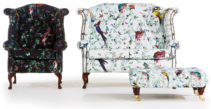 Skagfjord chesterfield armchair and sofa, in fabrics intricately decorated with foliage, butterflies and parrots