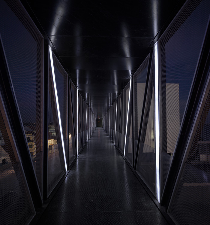 In the pedestrian bridge, neon lights are angled vertically or parallel to facets of the main volume