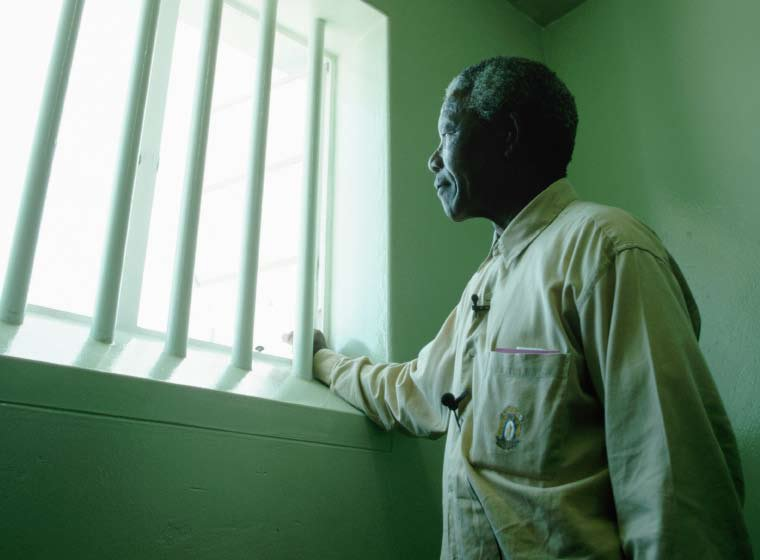 "Nelson Mandela pictured during a return visit to his cell on Robben Island. He wrote in his autobiography that tending his garden offered a ""small taste of freedom"""
